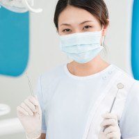 Vertical portrait of a smiling dentistry intern holding dental tools